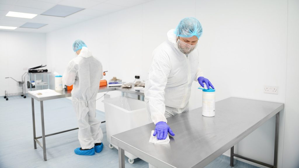 Photo of two people cleaning surfaces in a cleanroom
