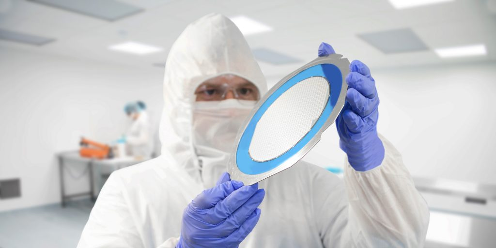 Photo of a water being held by a person in a cleanroom